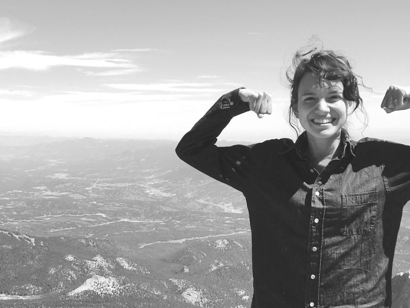 woman power posing on mountain in victory