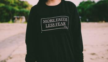 Girl wearing more faith less fear shirt